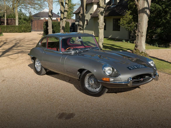An image of a dark green Jaguar E Type, parked in a gravel driveway to a beautiful country house.